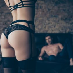 Close up cropped photo of beautiful sexy, naughty, fantasy, elegant, charming, slim, desired, sensual sexually stimulating curves on woman's ass wearing lace black underwear, the guy is lying in bed